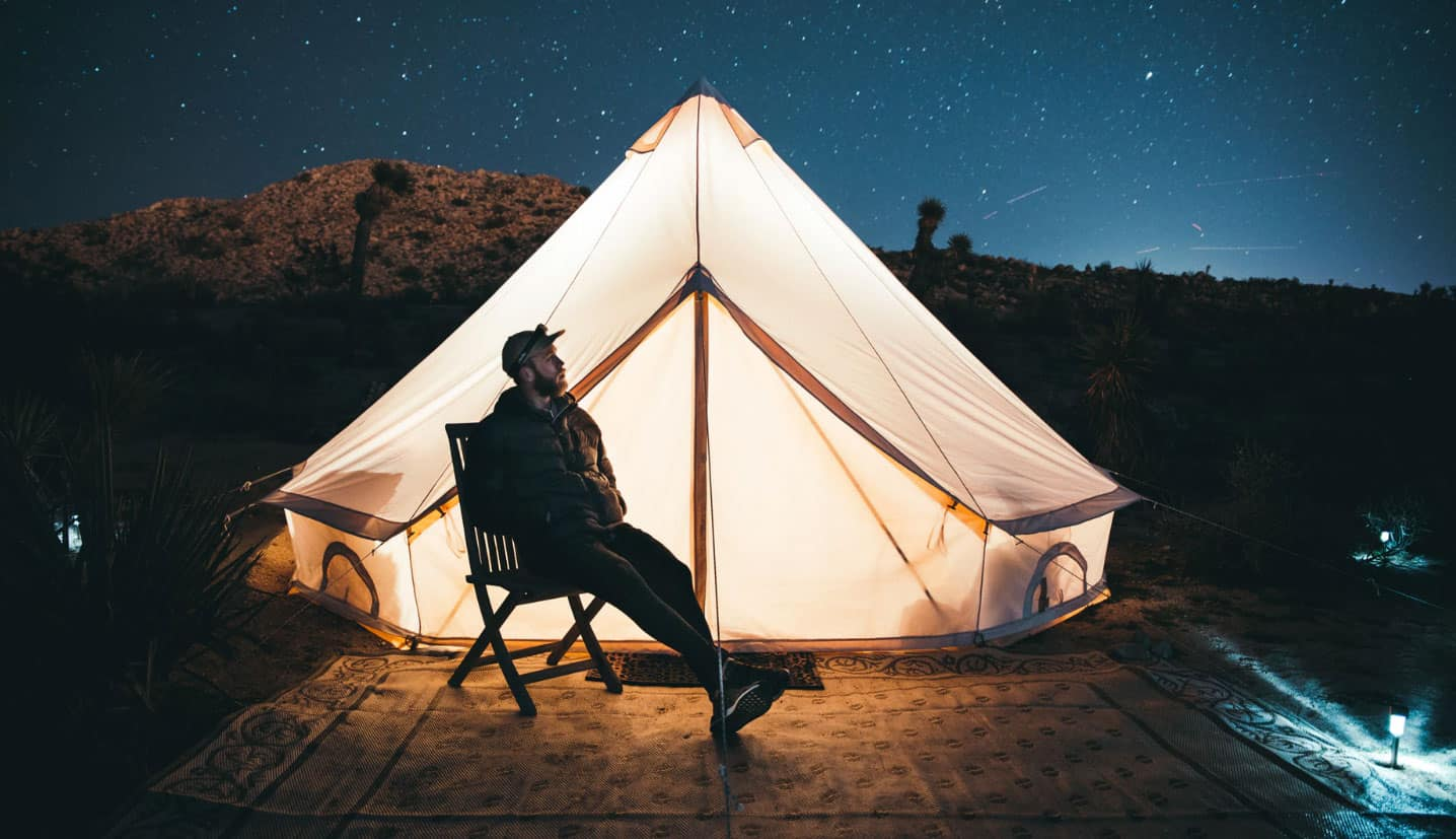 man-sitting-by-tent-with-light
