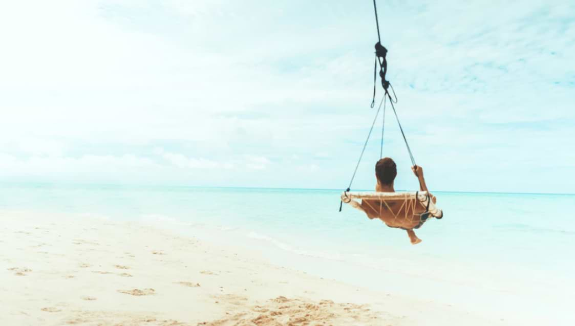 man swing beside body of water
