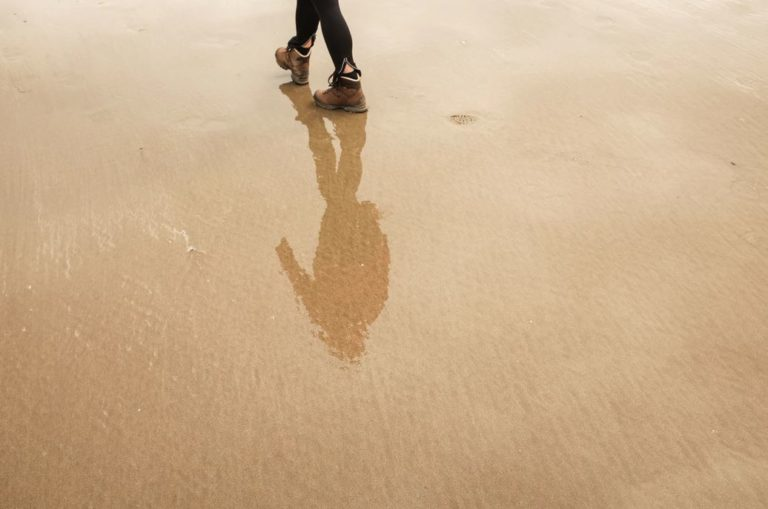 reflection of a man on wet sand